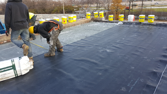 Installing and fully adhering the new .90mil EPDM membrane.